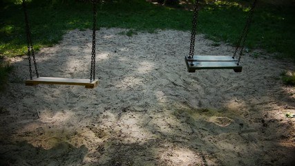 Two empty swings in a playground.