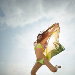 Young attractive girl on beach jumping with Brazil flag