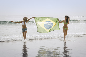 Young attractive girls on beach running with Brazil flag