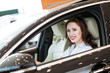 young woman in the new car in the showroom