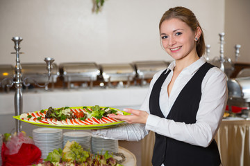Catering service employee posing with tray for buffett