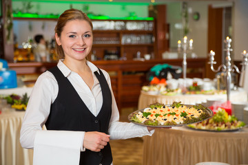 Catering service employee or waitress with a tray of appetizers