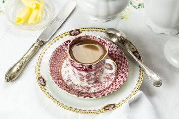 Antique porcelain breakfast setting with white coffee on white c