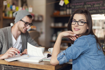 Stylish woman studying with her friend at cafe