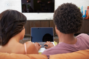 Rear View Of Couple Sitting On Sofa Using Laptop