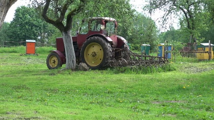 retro tractor and beehive in old farm spring garden