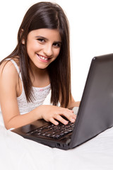 Girl with laptop on bed