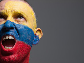 Man face painted with colombian flag.