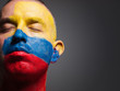 Man and his face painted with the flag of Colombia.