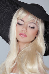 Beautiful young woman with long blond hair wearing in hat. Prett