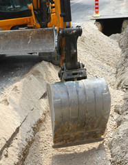 bucket of a bulldozer during the digging in the road in the city