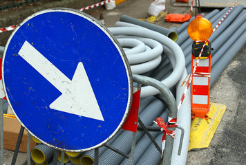 big blue sign with white arrow during excavation work on the str
