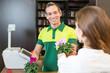 Ein Verkäufer in Blumenladen verkauft einer Kundin eine Blume