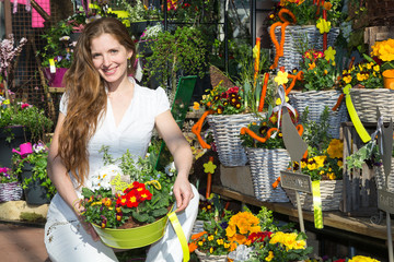 Kundin in Blumenladen mit Blumen und Gestecken