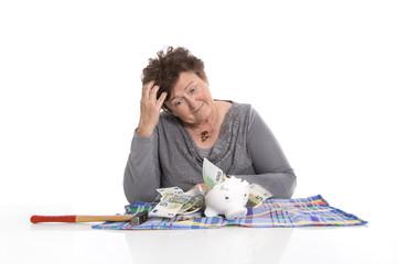 Großmutter isoliert mit Sparschwein und gespartem Geld