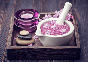 Sea salt in mortar, Zen massage stones and lilac flowers. Spa.