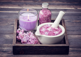 Sea salt, candle and lilac flowers.