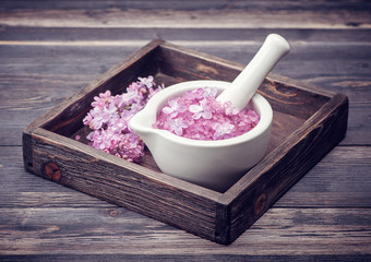 Sea salt in mortar and lilac flowers. Spa.