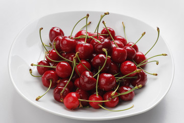 Cerezas rojas en un plato blanco