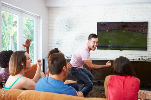 Group Of Friends Sitting On Sofa Watching Soccer Together - 65241565