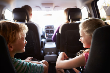 Children In Back Seat Of Car On Journey With Parents