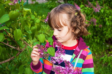 Portrait of sad little girl among the flowers of lilac