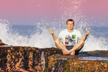 man meditating in a yoga pose on a rock
