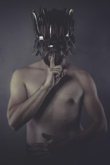 Shut, naked man with crown made of silver forks and knives