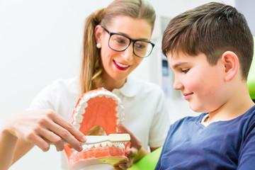 Zahnärztin erklärt Junge richtiges Zähneputzen