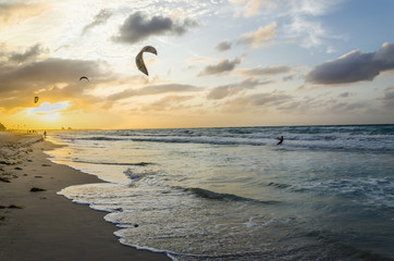 Professional kiter makes the difficult trick on a sunset