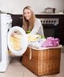woman with linen basket near washing machine