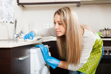 Blonde woman cleaning  furniture in kitchen