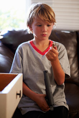 Boy Playing With Parent's Gun He Has Found At Home