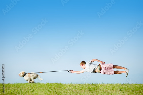 Leinwanddruck Bild Hund an Leine mit fliegendem Hundebesitzer