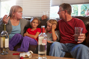 Parents Arguing On Sofa With Children Smoking And Drinking