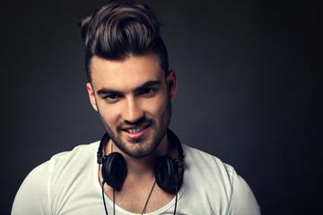 Handsome DJ posing in studio on dark background with headphones