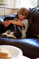 Unhappy Boy Sitting On Sofa At Home