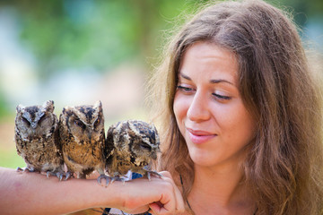 girl holding on a hand of beautiful owls