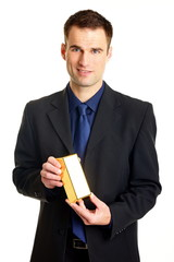 Handsome businessman in suit holds and shows gold brick