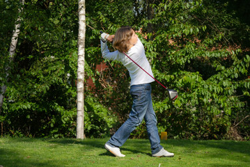 Young golf player with driver teeing-off from tee-box