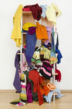 Messy winter clothes thrown on a shelf.Untidy cluttered wardrobe poster