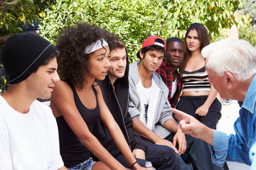 Senior Man Talking With Gang Of Young People