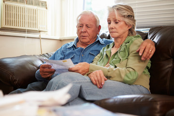 Worried Senior Couple Sitting On Sofa Looking At Bills