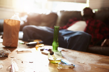 Man Slumped On Sofa With Drug Paraphernalia In Foreground