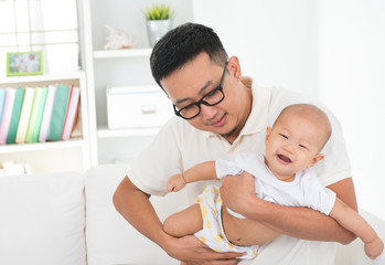 Asian family lifestyle at home. Father flying baby boy, having f