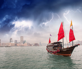 Sailing ship crossing the sea near a city during a storm