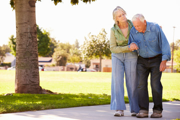 Senior Woman Helping Husband As They Walk In Park Together