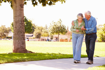 Senior Man Helping Wife As They Walk In Park Together