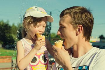 Девочка с папой кушает мороженое летом на улице