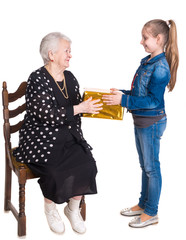 Granddaughter giving gift to her grandmother